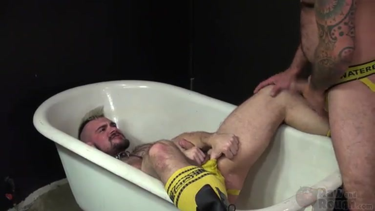 aarin lies back in bathtub while scotty rage takes a piss