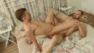 burly man lies back while horny guy rides his uncut dick
