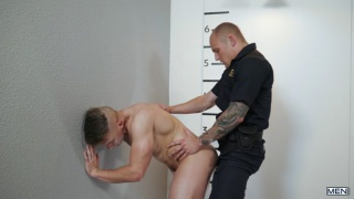 cop bends over an offender during his mugshot photos