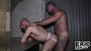 rugged bald man wearing only a jockstrap gets fucked in a bar