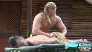blond masseur stretches twink on the massage table