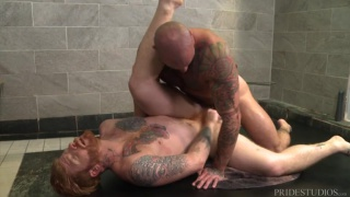ginger guy sucks a bald man's cock in the gym shower