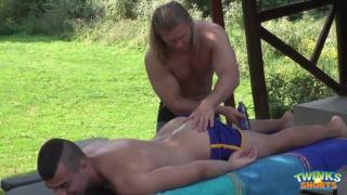 blond masseur strokes off his dark-haired client