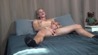 blond guy holds his balls while jerking quickly