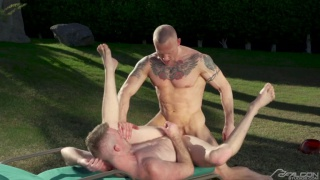bald muscle inked hunk fucks a blond guy outdoors