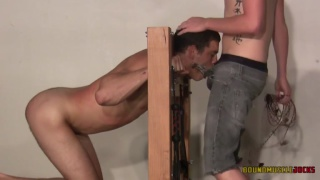 slave locked in stocked gets his back flogged