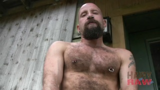 Pig in rubber plays with cock