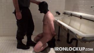 slave kneeling on wetroom floor at iron lockup